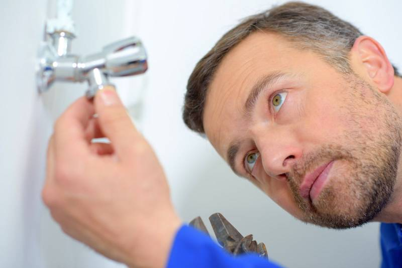 man fixing the shower head